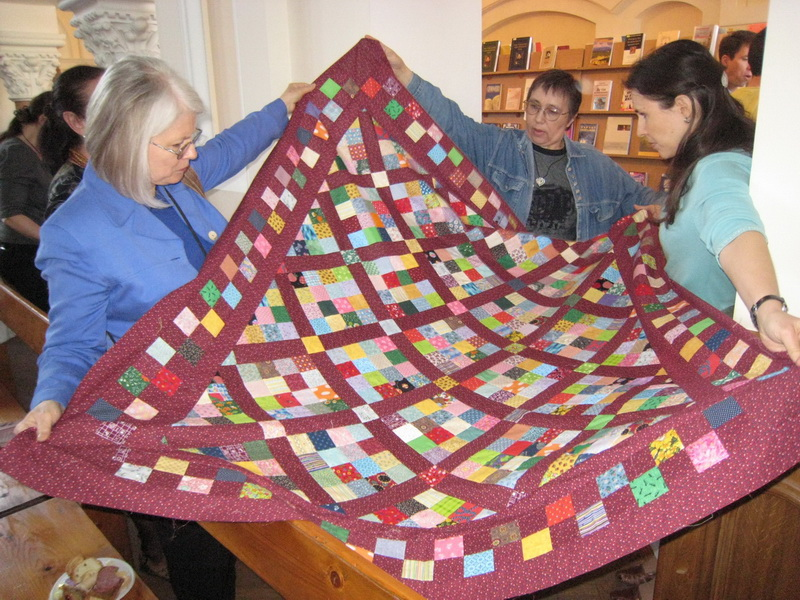 Darlene, Jhenya & Andrea with Quilt at church